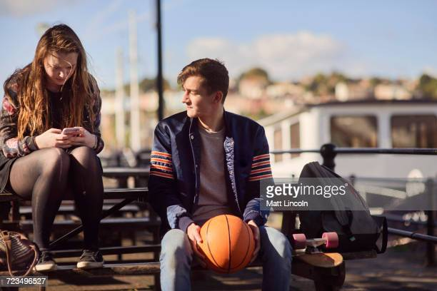 Two friends sitting outdoors, young man holding basketball, young woman using smartphone, Bristol, UK