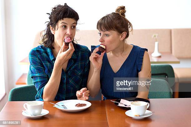 Two friends sitting side by side in a coffee shop eating cup cakes