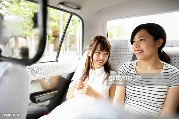 2 人の友人、タクシーの後部座席に並んで座って会話します。