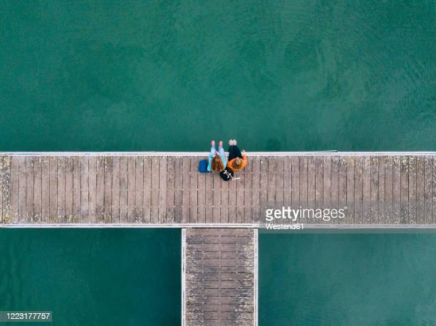 two friends sitting side by side on jetty, valdemurio reservoir, asturias, spain - chegada imagens e fotografias de stock