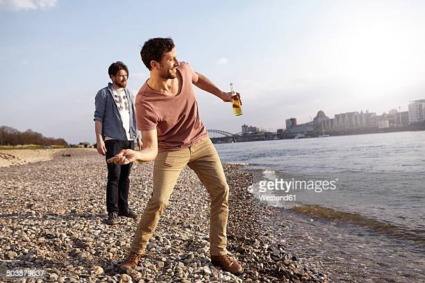Two friends skipping stones at river