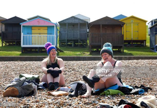 two friends smile on the beach - menopossibilities stock pictures, royalty-free photos & images