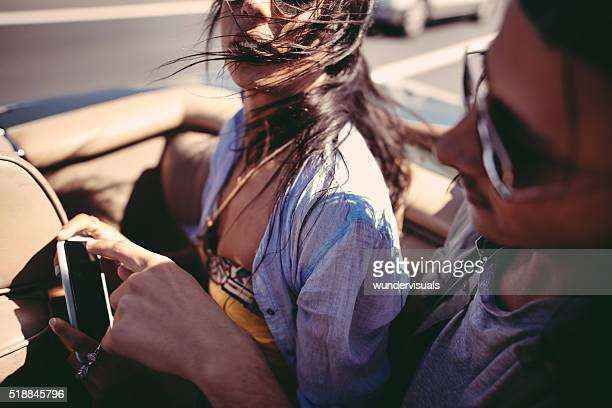 Two friends spending time with smartphone during a summer journey