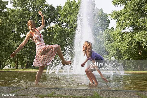 Two friends splashing in a fountain