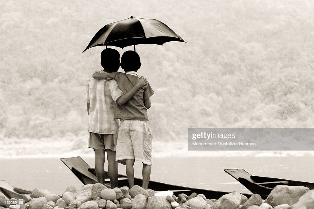 Two friends standing on river bank under umbrella : Stock Photo