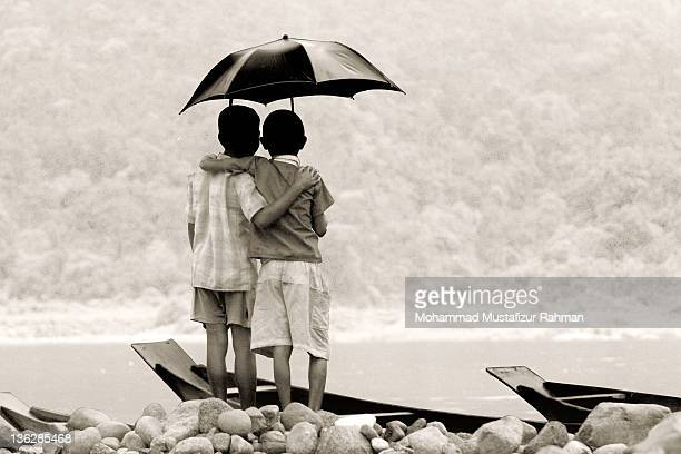 Two friends standing on river bank under umbrella