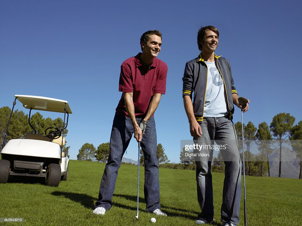 Two Friends Standing Together on a Golf Course : Stock Photo