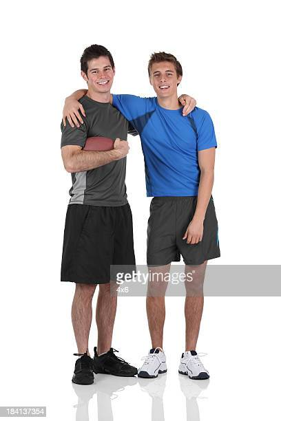 Two friends standing with a football