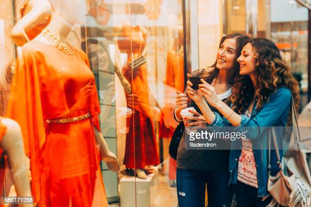 two friends taking a picture of a mannequin in a clothing store - orange dress stock pictures, royalty-free photos & images