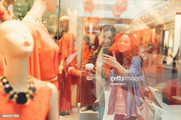 Two friends taking a picture of a mannequin in a clothing store
