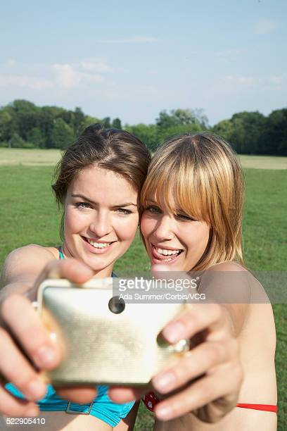Two friends taking picture of themselves with digital camera