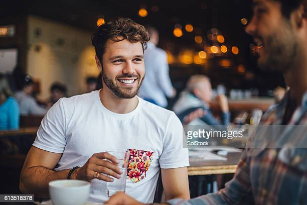 two friends talking in a cafe - jonge mannen stockfoto's en -beelden