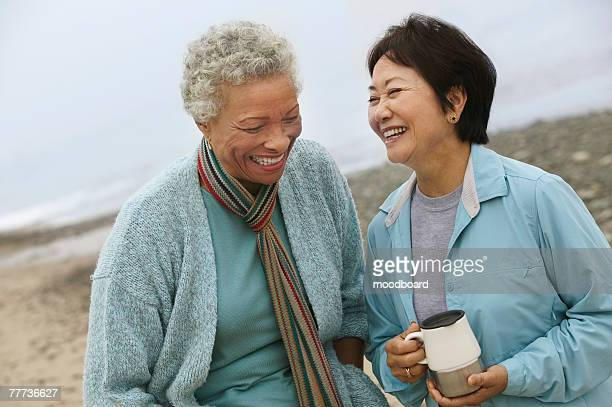 two friends talking over coffee on the beach - 50 59 years stock pictures, royalty-free photos & images