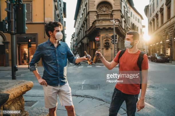 zwei freunde toasten zusammen im freien in der stadt tragen gesichtsmasken - corona beer stock-fotos und bilder