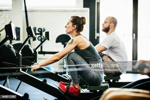 two friends using rowing machines at gym - fitnesseinrichtung stock-fotos und bilder