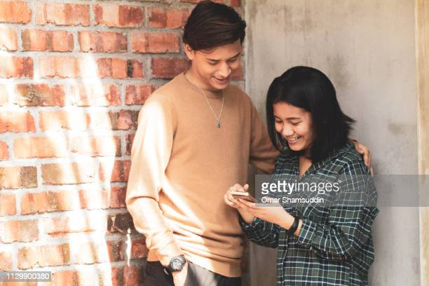 Two friends using smart phone outside the house