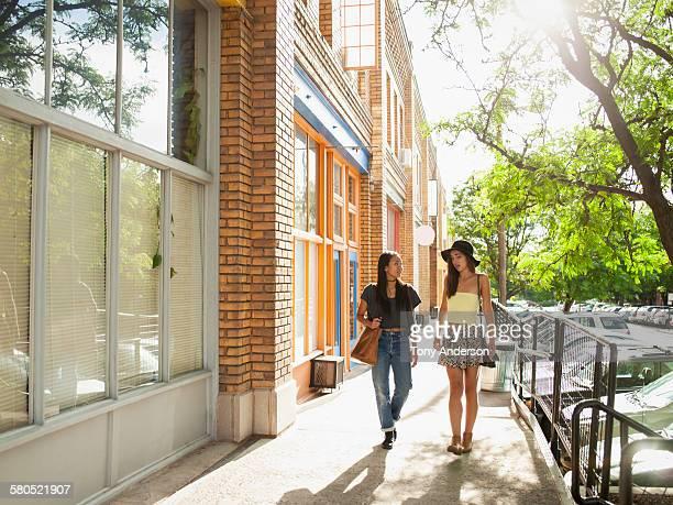 Two friends walking in city shopping area