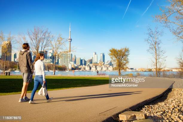 two friends walking in toronto trillium park with city skyline in the background - may stock pictures, royalty-free photos & images