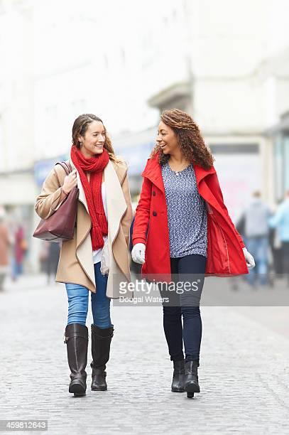 two friends walking on busy high street. - pañuelo rojo fotografías e imágenes de stock