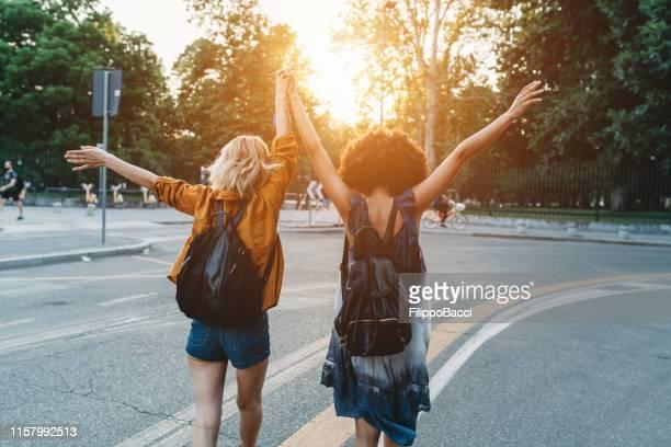 zwei freunde, die bei sonnenuntergang gemeinsam in der stadt spazieren gehen - frauenpower stock-fotos und bilder