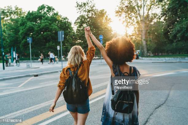 two friends walking together in the city at sunset - female friendship stock pictures, royalty-free photos & images