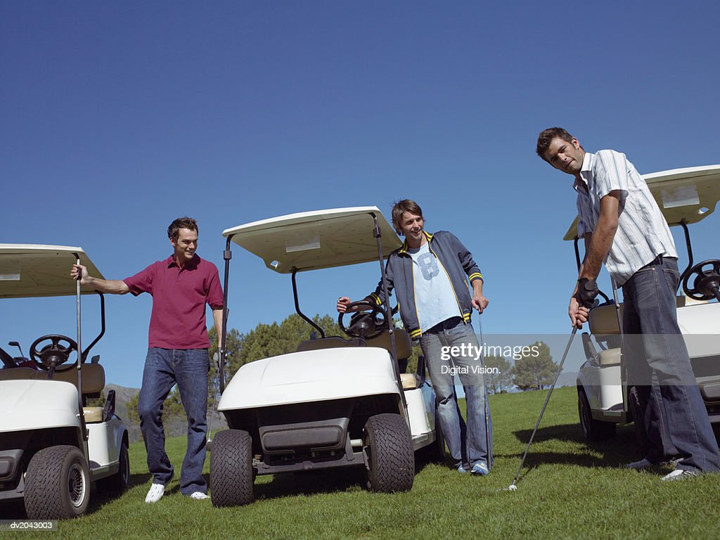 Two Friends Watching a Man Preparing to Take a Golf Swing : Stock Photo