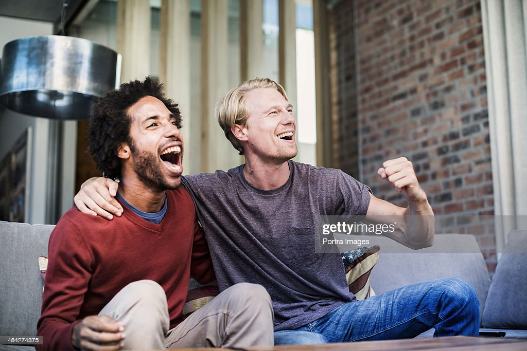 Two friends watching sports on tv : Stock Photo