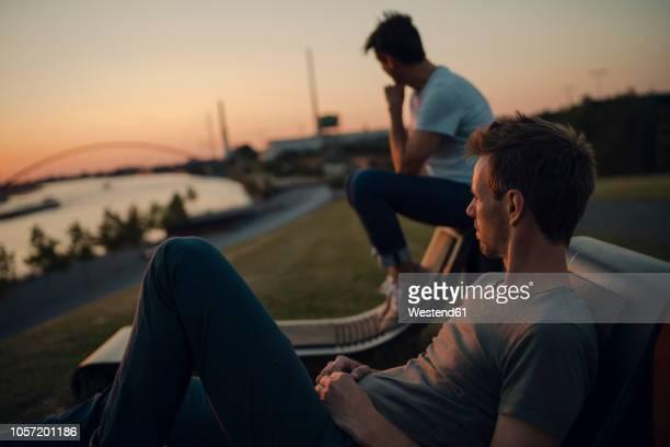 two friends watching sunset at the river - männerfreundschaft stock-fotos und bilder
