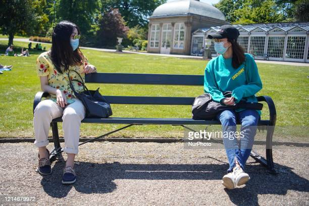 Two friends wearing face masks sit on a bench as they maintain social distancing at the Botanical Gardens Sheffield UK on a warm day on 22nd May 2020
