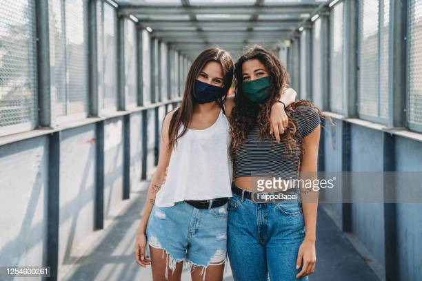 two friends wearing protective facemasks and looking at camera in the city - female friendship stock pictures, royalty-free photos & images
