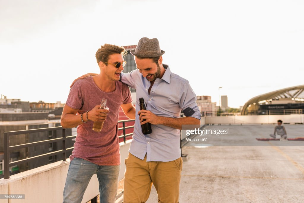Two friends with beer bottles on rooftop : Stock Photo