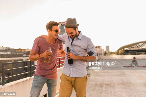 Two friends with beer bottles on rooftop