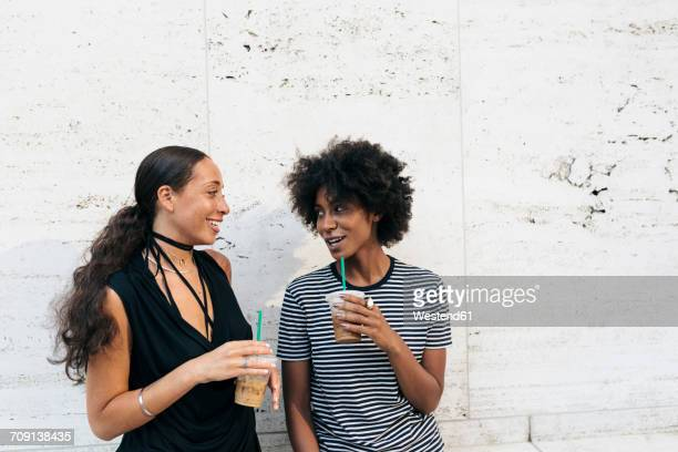 Two friends with drinks talking in front of a wall