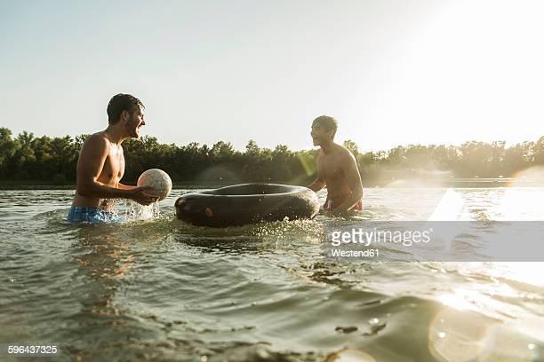 two friends with inner tube and ball in water - nur erwachsene stock-fotos und bilder