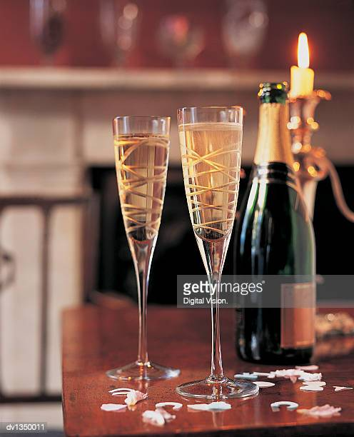 Two Full Champagne Flutes, a Bottle of Wine and a Candle on a Table