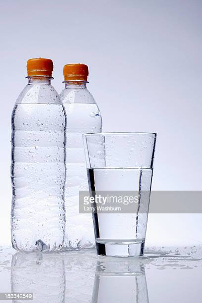 Two full plastic water bottles and a drinking glass
