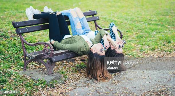 two funky girlfriends having fun and  lying upside down on a bench in park - blonde long legs stock pictures, royalty-free photos & images