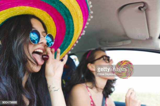 two funny cheerful hipster women traveling in car - mexican hat stock pictures, royalty-free photos & images