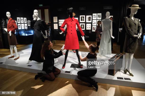 Two gallery assistants pose with Valentino Couture red dress coat during a preview of items from the sale of actrees Audrey Hepburn's personal...