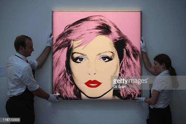 Two gallery technicians adjust a painting by Andy Warhol entitled 'Debbie Harry' in Sotheby's auction house on June 17 2011 in London England The...