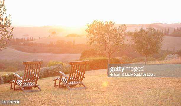 Two garden deck chairs and sunrise landscape, Tuscany, Italy