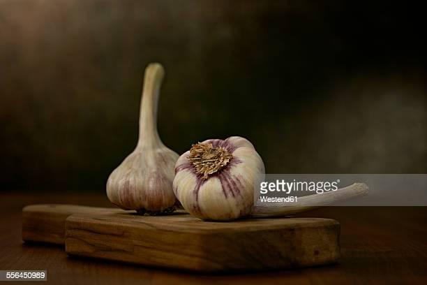 Two garlic bulbs on wooden board
