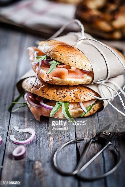 Two garnished home-baked bagels wrapped in paper and scissors on wood