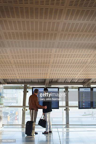 two gay men at airport looking at departure board