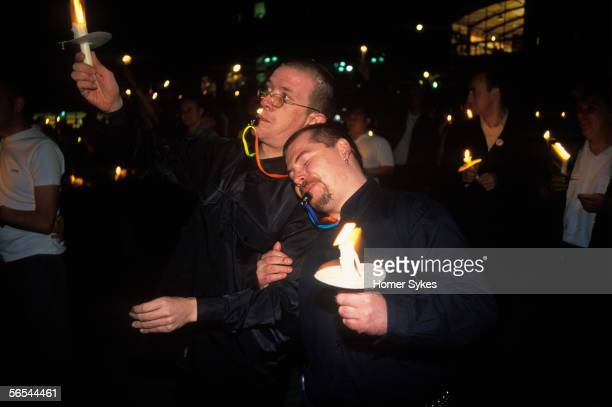 MANCHESTER LANCASHIRE ENGLAND AUGUST 1999 Two gay men console each other as they hold lighted candles aloft during a vigil in Sackville Park for gay...