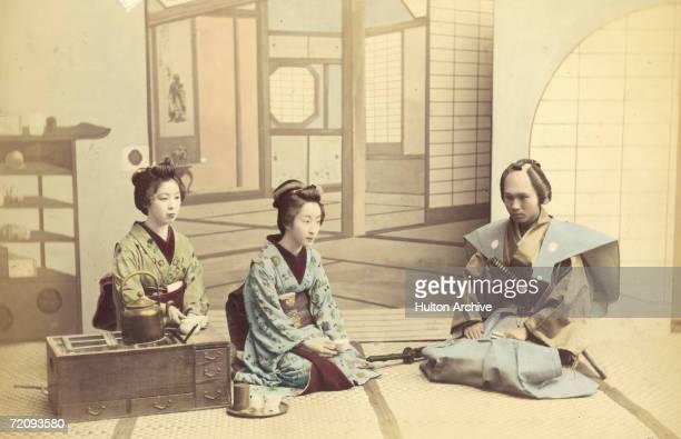 Two geishas receive a visiting samurai Japan circa 1880