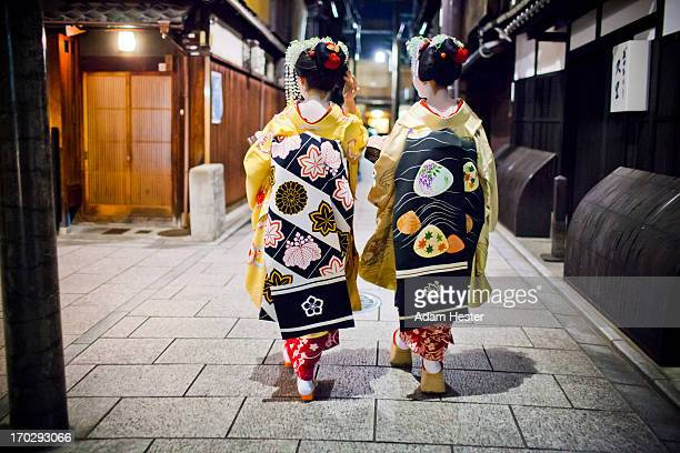 Two Geishas walking together at night.