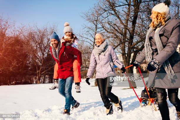 Two Generation Family Having Fun Outdoors At Winter