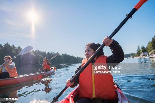 two generation multi-ethnic family kayaking and canoeing in remote inlet - outdoor pursuit stock pictures, royalty-free photos & images