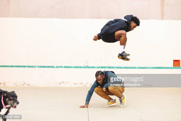 two generation z males having fun and messing around on a hand ball court with pet dog photo series - canine stock pictures, royalty-free photos & images